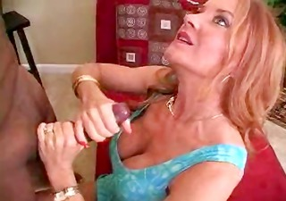 MILF redhead performs a handjob on a black guys